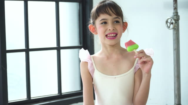 smiling of ballerina student eating watermelon-shaped ice cream in ballet class - dance studio stock videos & royalty-free footage