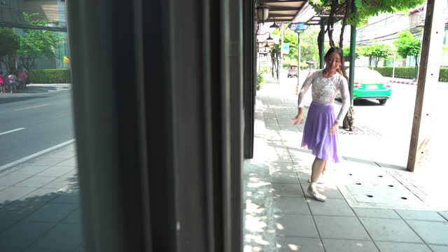 vídeos de stock, filmes e b-roll de sorrindo de orgulho sobre a bela bailarina asiática de cor branca e violeta praticando dançar com emoção positiva e sorrindo em um caminho de pedestres uma paisagem urbana, bangkok, tailândia. conceito da jovem ativa no fim de semana. - 20 29 years