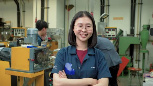 vídeos de stock, filmes e b-roll de sorrindo de jovem engenheiro asiático trabalhando em uma linha de produção de polímeros para produzir extrusor de polímeros usando extrusor de dois parafusos. mulher engenharia, estudante cientista vestindo roupas azuis tem orgulho de fazer experiment - operário de linha de produção