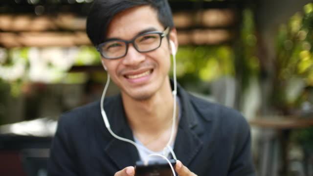 stockvideo's en b-roll-footage met glimlachen van jonge man muziek beluisteren door slimme telefoon - in ear koptelefoon