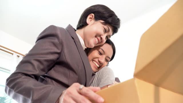 sorridente di giovane donna con coppia omosessuale mentre apre una scatola di cartone - box container video stock e b–roll