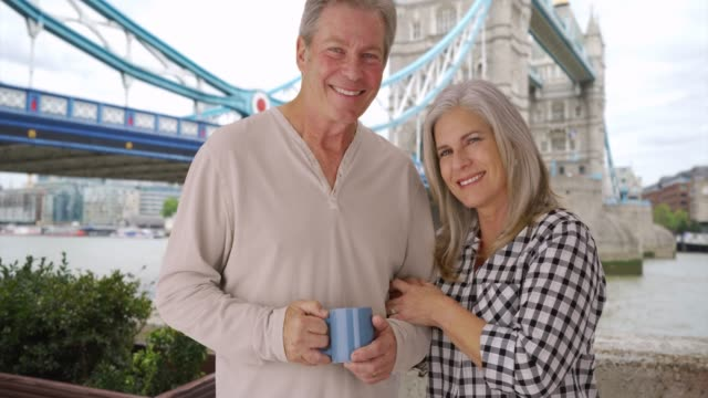 smiling old white couple looks at camera near tower bridge in london - weitere themen stock-videos und b-roll-filmmaterial