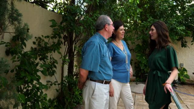 vídeos y material grabado en eventos de stock de ms smiling parents hanging out with adult daughter during backyard family party - encuadre de tres cuartos