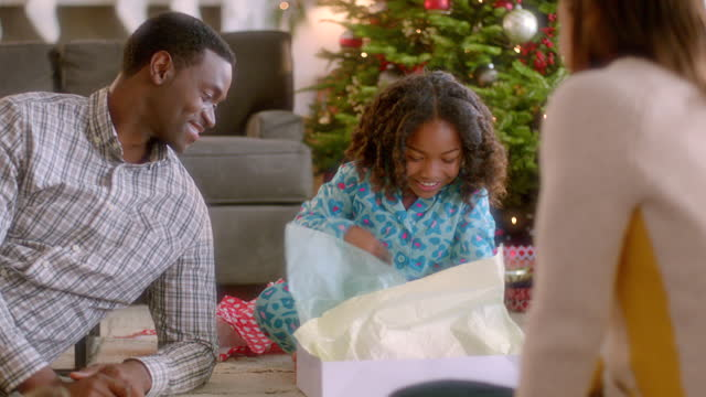 smiling parents watch as girl unwraps christmas present and admires new pink sweater (dolly-shot) - unwrapping stock videos & royalty-free footage