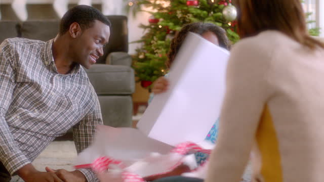 smiling parents watch as girl unwraps christmas present (dolly-shot) - wrapping paper stock videos & royalty-free footage
