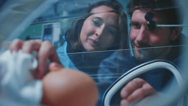 smiling parents with newborn baby in incubator - admiration stock videos & royalty-free footage