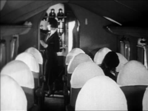 B/W 1933 smiling passengers entering airplane cabin + sitting in seats of American Airlines plane