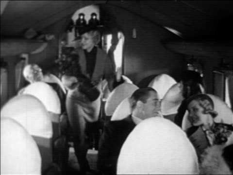 vídeos de stock e filmes b-roll de b/w 1933 smiling passengers entering airplane cabin + sitting in seats - sentar se