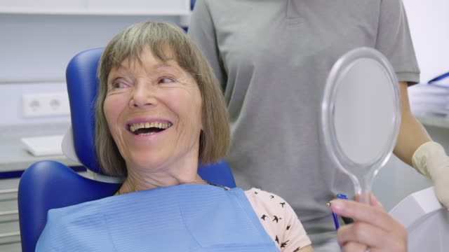 smiling patient talking while holding hand mirror - dentist stock videos & royalty-free footage
