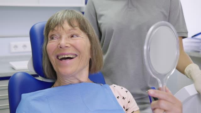 vídeos de stock, filmes e b-roll de fala paciente de sorriso ao segurar o espelho de mão - dentista