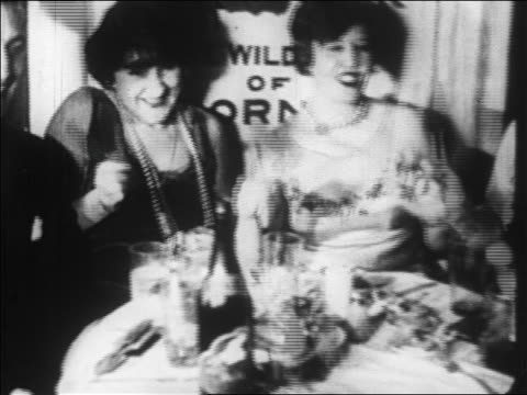 b/w 1928 pan smiling people at table in nightclub shaking noise makers / newsreel - 1928 stock-videos und b-roll-filmmaterial