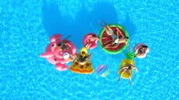 AERIAL: Smiling people playing with a ball on fun inflatable floaties in pool