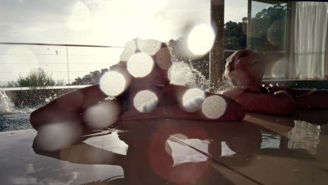stockvideo's en b-roll-footage met glimlachende mensen ontspannen in een pool - binnenbad
