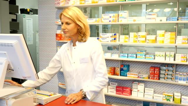 vídeos de stock, filmes e b-roll de farmacêutico sorridente usando caixa registradora em farmácia - caixa registradora
