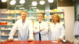 Smiling pharmacists at checkout counter in store