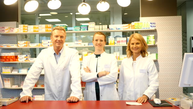 smiling pharmacists at checkout counter in store - laboratory coat stock videos & royalty-free footage