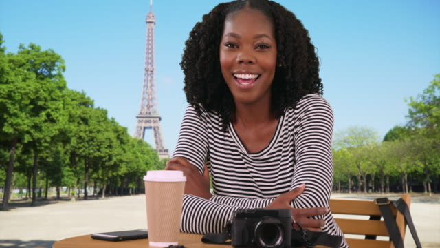 smiling portrait of beautiful black woman relaxing at table near eiffel tower - minnesmärke bildbanksvideor och videomaterial från bakom kulisserna