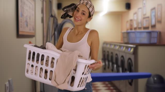 smiling portrait of cute hispanic woman holding laundry basket - tvättmedel bildbanksvideor och videomaterial från bakom kulisserna