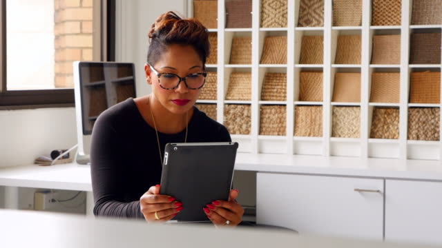 MS Smiling portrait of female business owner working on digital tablet in office