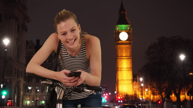 smiling portrait of pretty caucasian girl in london at night - big ben点の映像素材/bロール