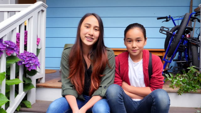 ms zi smiling portrait of sisters on front steps of home waiting for ride to school - coda di cavallo video stock e b–roll