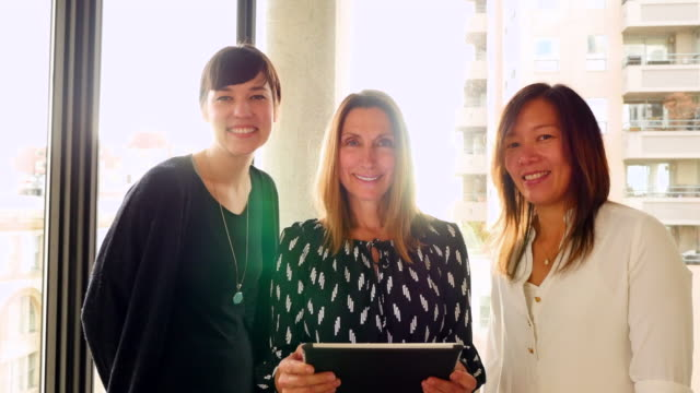 MS Smiling portrait of three businesswomen reviewing project on digital tablet