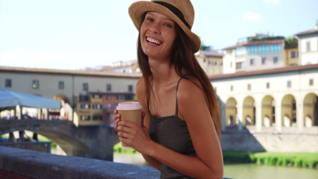 smiling portrait of tourist woman enjoying coffee by the ponte vecchio bridge - ponte点の映像素材/bロール