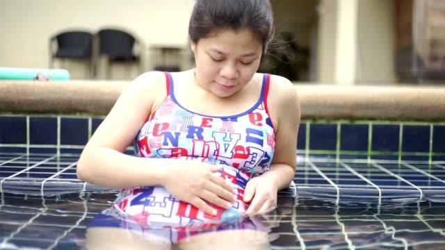 ler gravid asiatisk kvinna avkopplande i poolen. - utebassäng bildbanksvideor och videomaterial från bakom kulisserna