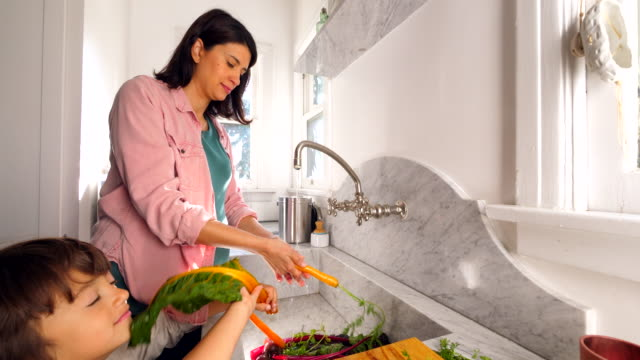 ms smiling pregnant mother washing organic vegetables in kitchen with son - hygiene stock videos & royalty-free footage