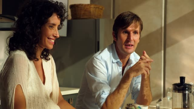 ms smiling pregnant wife in discussion with husband while sitting in kitchen - real wife sharing stock-videos und b-roll-filmmaterial