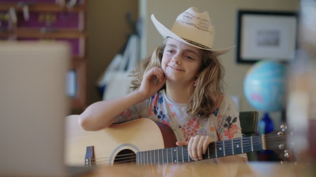 smiling pre-teen girl looks at laptop during online guitar lesson - cowboy hat stock videos & royalty-free footage