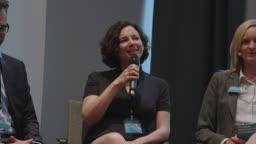 Smiling professionals during seminar in auditorium