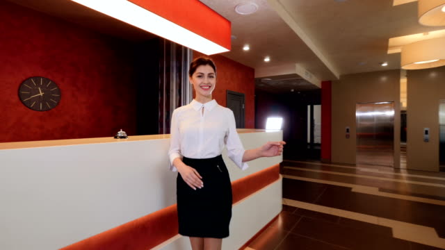 Smiling receptionist at hotel reception desk meet guests. 4K.