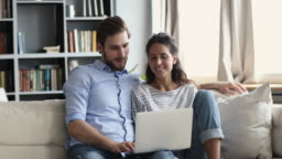 Smiling relaxed young couple using laptop at home on couch