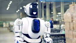 Smiling robot is walking forwards in factory premises