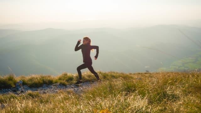 Smiling runner running over rocky trails and grassy slopes