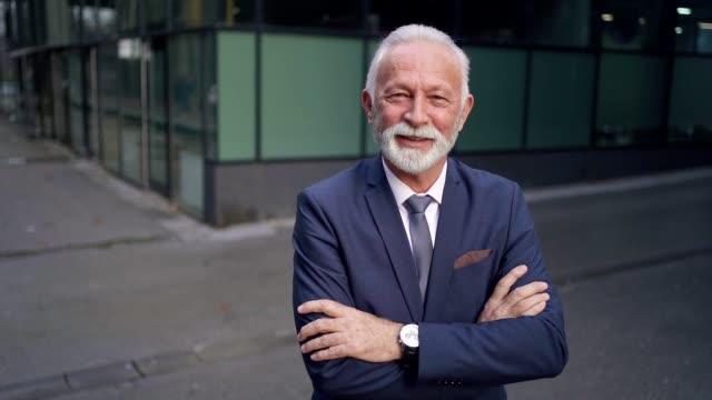 lächelnder senior geschäftsmann - weiser mann stock-videos und b-roll-filmmaterial