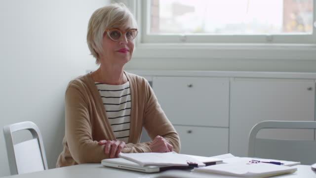 vidéos et rushes de ms smiling senior businesswoman sitting at table in office conference room - retraite
