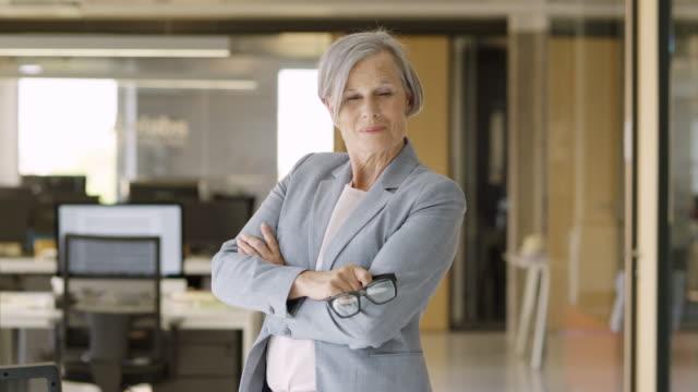 vídeos de stock, filmes e b-roll de mulher de negócios senior sorridente com os braços cruzados - mulher de negócios