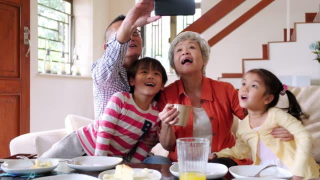 vídeos de stock, filmes e b-roll de sorridentes avós chineses idosos tirando selfie em casa com netos - família de várias gerações