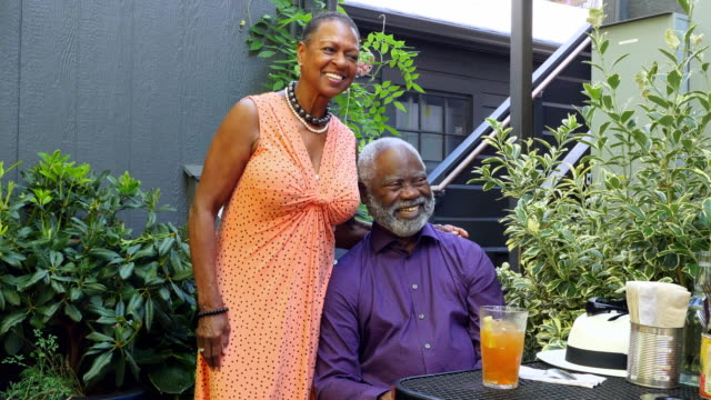 MS Smiling senior couple at outdoor cafe on summer afternoon