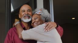Smiling senior couple embracing at doorway