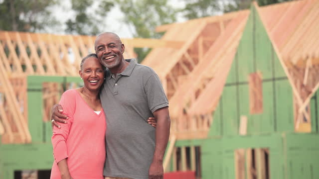 Smiling senior couple hugging in front of house under construction