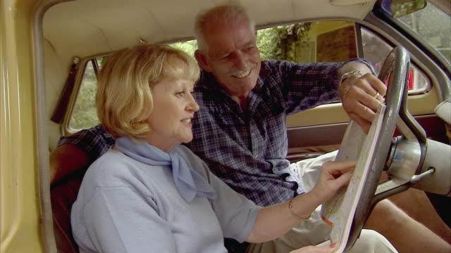 stockvideo's en b-roll-footage met ms, smiling senior couple looking at map in car, tamborine mountain, brisbane, queensland, australia - passagiersstoel