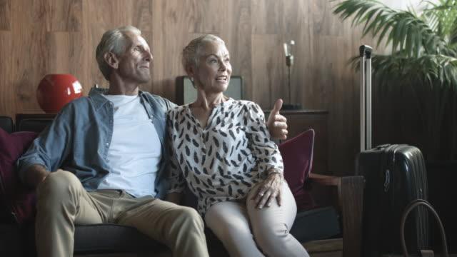 vidéos et rushes de smiling senior couple on couch, medium shot - retraite