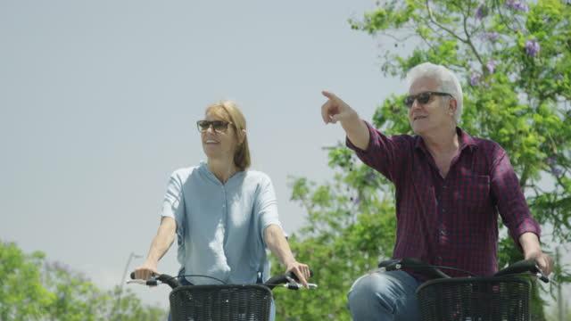vídeos y material grabado en eventos de stock de pareja de ancianos sonrientes montando en bicicleta en la calle durante un día soleado - 60 69 años