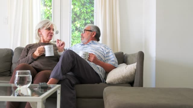 smiling senior couple with coffee cups talking while sitting on a sofa - senior couple stock videos & royalty-free footage