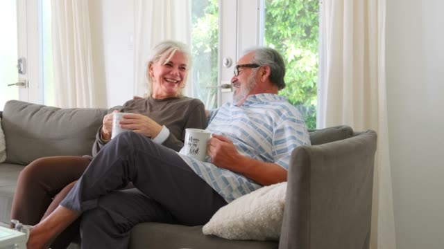 Smiling senior couple with coffee cups talking while sitting on a sofa