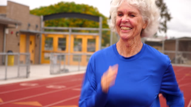 ts smiling senior female athletes race walking on track - athleticism stock videos & royalty-free footage