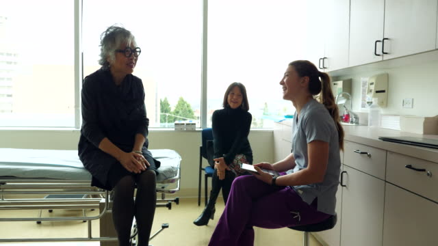 ms smiling senior female patient in discussion with nurse during check up in exam room - clinic stock videos & royalty-free footage